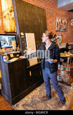 Bildende Künstlerin Katie Maher referenzieren Computer während der Erstellung eines Öl Malerei in ihrer Galerie; Salida, Colorado, USA - Stockfoto