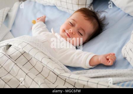 Lächelnden Mädchen liegen auf einem Bett schlafen auf blaue Blätter - Stockfoto