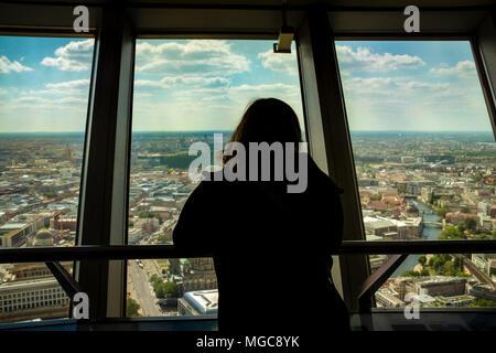 Silhouette von Rückseite der Frau durch ein Fenster an der Berliner Skyline der Stadt. Blick von innen auf den Fernsehturm Gebäude. - Stockfoto