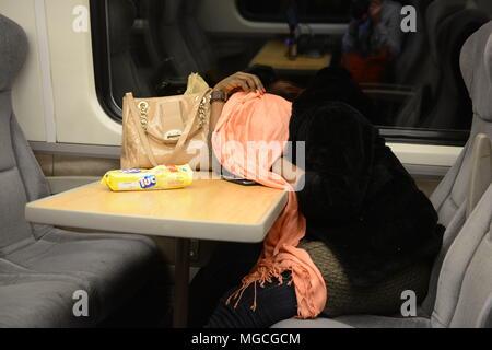 Frau auf Zug, ruhender Kopf am Tisch, Kopf und Gesicht mit Schal abgedeckt - Stockfoto
