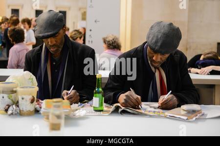 Zwei eineiige Zwillinge, im Café sitzen, die gleiche Kleidung trägt, Schreiben mit beiden Händen gleichzeitig, London, England, Großbritannien - Stockfoto