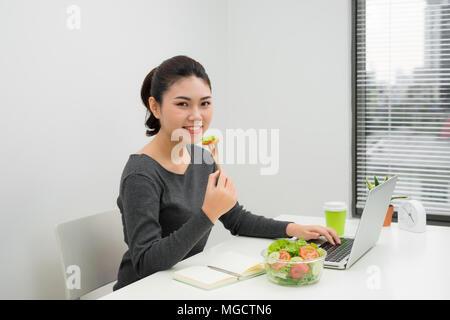 Frau hat gesundes Business Lunch in modernen Büro Interieur. Junge schöne Geschäftsfrau am Arbeitsplatz, Essen Salat in der Schüssel, Diät und v - Stockfoto