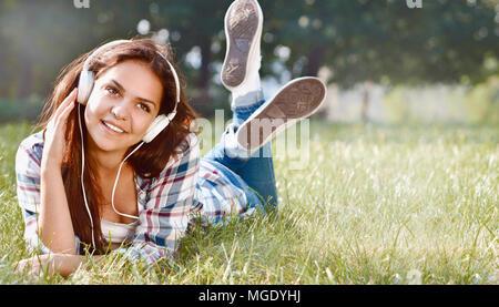 Porträt der jungen Mädchen Musik hören im Gras liegen. Cute Jugendmädchen Relaxen im Park - Stockfoto