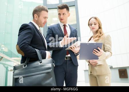 Ernsthafte zuversichtlich, dass junge männliche Manager Strategie für Business Development und teilen es mit Chef im Büro, weibliche Business Assistant showin - Stockfoto