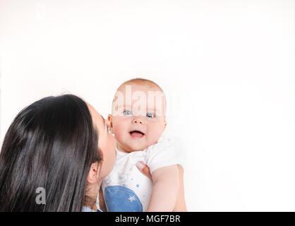 Mamma kissing ihr Sohn auf einem weißen Hintergrund. Neugeborene in die Kamera schaut. Glückliche Mutterschaft Konzept - Stockfoto
