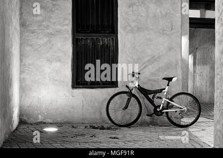 Vintage Bike auf der Straße gegen die Wand eines alten Gebäudes lehnte sich mit einem antiken Fenster - Stockfoto