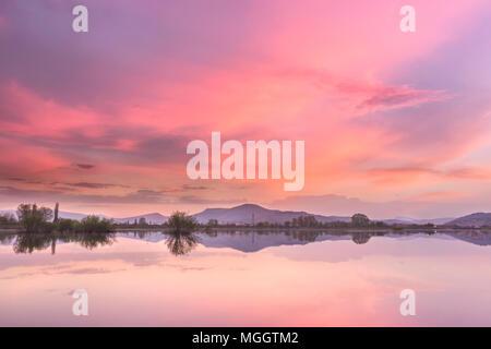 Brennen von Pirot Stadtbild sonnenuntergang himmel über künstliche reflektierende See und rosa, orange Fluffy Clouds - Stockfoto