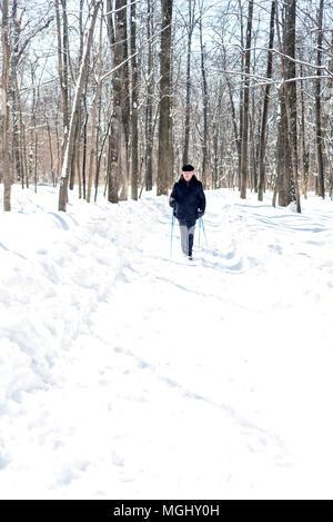 UFA, Russland, 29. MÄRZ 2018 - Ältere Menschen im Winter Kleidung geht mit Nordic Walking Stöcke durch einen Waldweg in schneefall Einsatz der Stöcke zu im - Stockfoto
