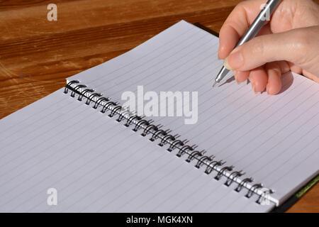 Frau mit Stift in der Hand, balanciert, in einer Spirale gebundenes Notizbuch zu schreiben - Stockfoto