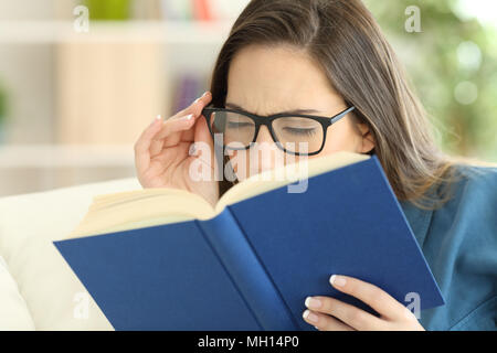 Frau mit einer Überanstrengung der Augen ein Buch lesen Brille zu Hause tragen - Stockfoto