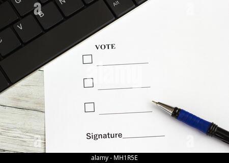 Stift zum Schreiben auf Holztisch mit einem Dokument für die Stimmabgabe und die Tastatur - Stockfoto