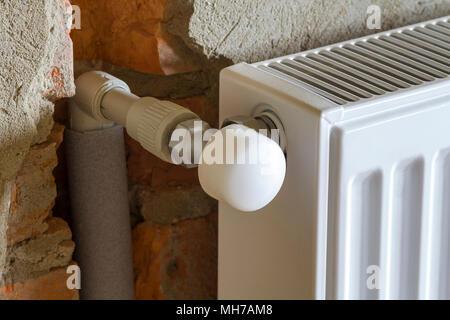 Close-up Seite Blick auf isolierte Heizung Kühler auf Stein rauh verputzten Wand in einen leeren Raum in eine neu gebaute Wohnung oder Haus installiert. Construc - Stockfoto