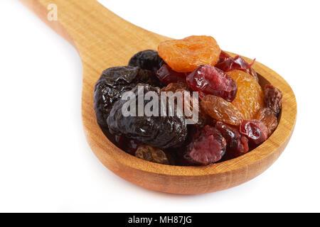 Mischung aus getrocknetem Obst (Pflaumen, Rosinen, Aprikosen und Cranberries) Löffel aus Holz auf weißem Hintergrund - Stockfoto