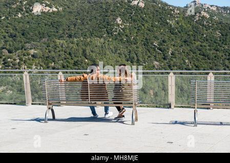 Junges Paar in Liebe, die auf einer Bank sitzen Natur der Insel Sardiniens genießen, Sardinien ist die italienische Insel unter Korsika Was gehört zu Frankreich - Stockfoto