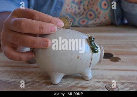 Tausendjährige Frau, eine 2 € Münze in ein Sparschwein aus Keramik - Stockfoto