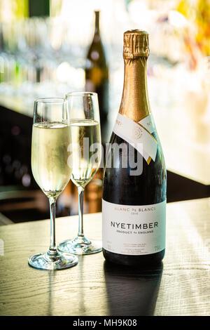 Nyetimber Flasche Champagner und zwei gefüllte Champagnergläser auf einem Tisch, unscharfer Hintergrund. - Stockfoto