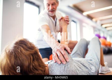 Leitender Physiotherapeut arbeitet mit einem weiblichen Patienten. - Stockfoto