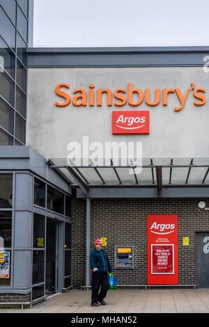 Eine orange Sainsbury's und rote Zeichen - die zwei Einzelhändler im Jahr 2016 zusammengeschlossen haben, - Stockfoto