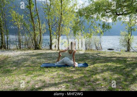 Junge Frau trainieren Yoga durch den See und die Berge, im Kanton Tessin, Schweiz, Europa erschossen. Menschen Entspannung Wohlbefinden Konzept - Stockfoto