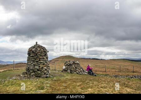 Walker eine Pause auf dem Gipfel des Besen fiel, mit dem Blick in Richtung Herren Sitz, Lake District, Cumbria, Großbritannien - Stockfoto