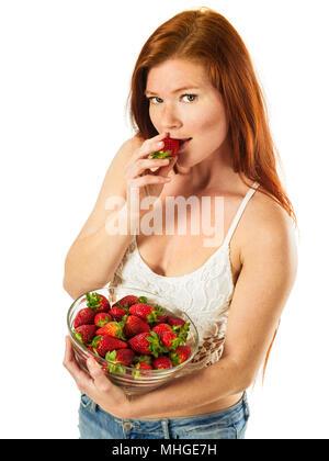 Foto von eine wunderschöne junge Frau mit langen roten Haaren Holding eine Schüssel Erdbeeren auf weißem Hintergrund. - Stockfoto