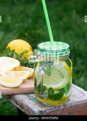 Hausgemachte Limonade mit Minze und Eis auf eine Holzbank im Garten. Im rustikalen Stil. - Stockfoto