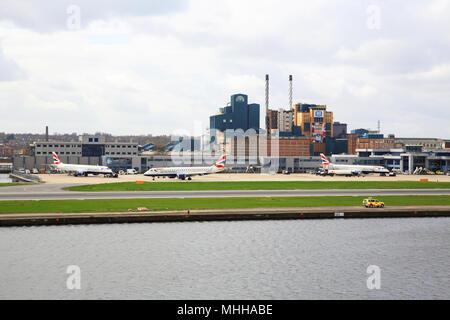 London City International Airport, in der königlichen Docks mit der Tate & Lyle Fabrik hinter, im Osten von London, England, Großbritannien - Stockfoto