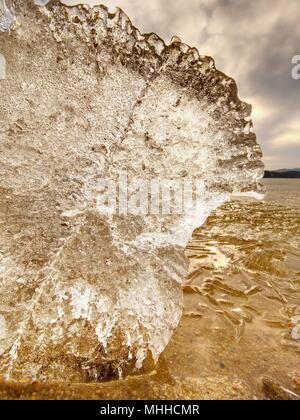 Eisschmelze am Sandstrand. Detail der Eisscholle mit tiefe Risse im Inneren. Das Ende der crue Winter kommen. - Stockfoto