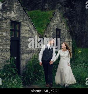 Junge stilvolle Mode Paar in Liebe in Island. Frau und Mann umarmen und möchten einander zu küssen. Stein Berge und isländischer Haus im Hintergrund. - Stockfoto