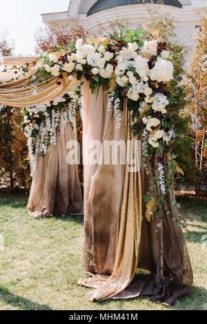 Bogen für die Trauung, dekoriert mit Tuch und Blumen - Stockfoto