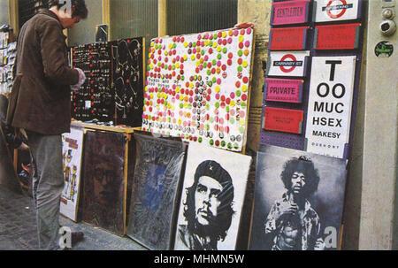 Abzeichen, Schmuck, die London Street Schilder und Poster von Bob Dylan, Che Guevara und Jimi Hendrix zum Verkauf auf Carnaby Street, schlagende Herz der Swinging Sixties in London. Datum: 1967 - Stockfoto