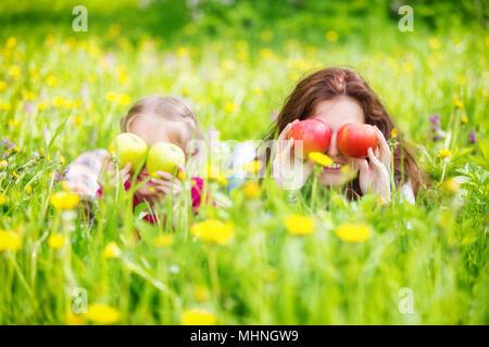 Mutter und Tochter auf der sonnigen Wiese mit Äpfeln in den Händen - Stockfoto