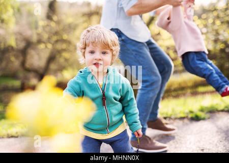Ein Vater mit seinem Kind Kinder draußen auf einer Feder. - Stockfoto
