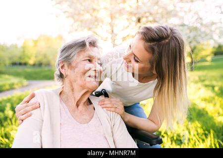 Ältere Großmutter im Rollstuhl mit Enkelin im Frühjahr die Natur. - Stockfoto