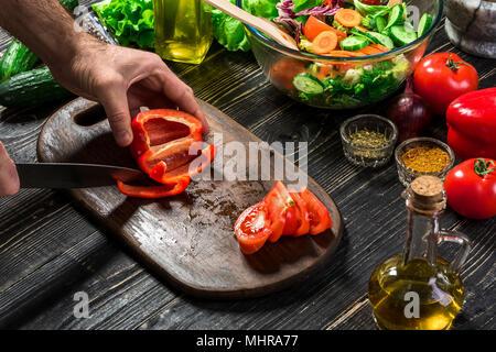 Des Menschen Hände schneiden rote Paprika mit Messer. Koch Schnitt rote Paprika. Mann liebt Kochen frischer Salat zum Abendessen. Paprika von Cook's Hand geschnitten. - Stockfoto