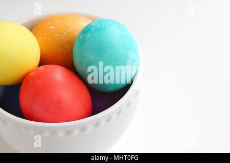 Hell Eier in einer weißen Schüssel auf weißem Hintergrund farbig - Stockfoto