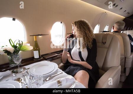 Geschäftsfrau Blick durch Fenster bei Reisen im Privatjet - Stockfoto