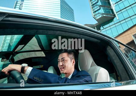 Der Geschäftsmann, der ein Auto fährt - Stockfoto