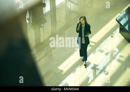 Junge Geschäftsfrau zu Fuß einen Anruf - Stockfoto