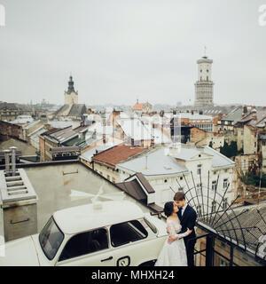 Braut und Bräutigam auf dem Dach in der Nähe der Alten retro Auto mit Panoramablick auf die Stadt - Stockfoto