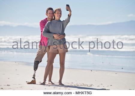Menschen mit künstlichen Bein Posieren für Selfie mit weiblichen Partner während der Sommer Strand Urlaub in Südafrika - Stockfoto