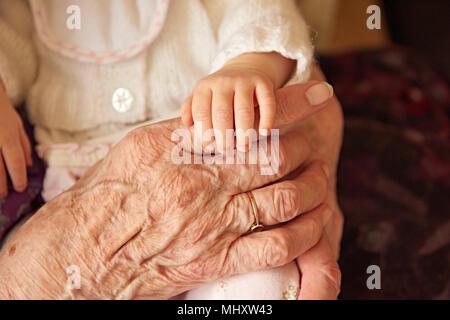 Ältere Frau mit Baby große Enkelin, in der Nähe der Hände - Stockfoto