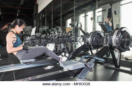 Frau, die Arbeiten in der Turnhalle, mit Rudergerät - Stockfoto