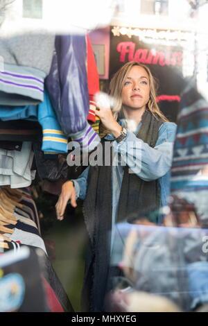 Junge Frau surfen Vintage Kleidung in Sparsamkeitspeicher - Stockfoto