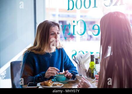Zwei weibliche Freunde sitzen zusammen im Café, Kaffee trinken - Stockfoto