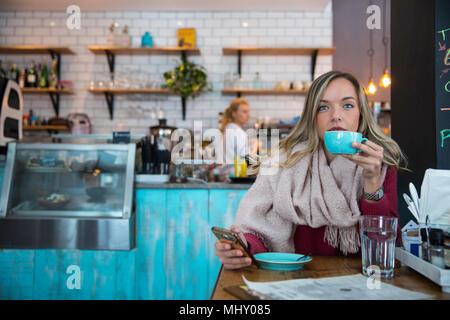 Frau sitzt im Cafe, Smartphone, trinken Kaffee - Stockfoto