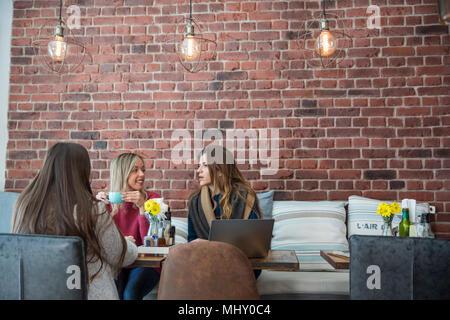 Weibliche Freunde im Cafe sitzen, Kaffee trinken, mit Laptop - Stockfoto