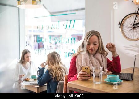 Frau sitzt im Cafe, Smartphone, Laptop vor ihr - Stockfoto