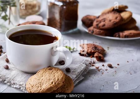Frühstück Hintergrund mit Porzellan Tasse frischen schwarzen Kaffee, hausgemachtem Oatmeal cookies, transparentes Glas Glas der Kaffeepulver auf weisser Baumwolle homespu - Stockfoto