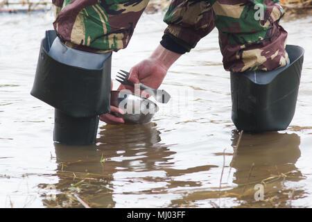 Mann in Gummistiefel Abwasch im Fluss Wasser - Stockfoto